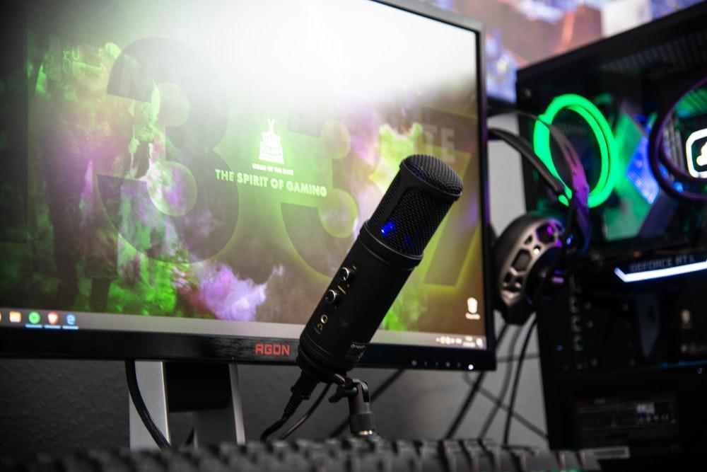 black microphone beside black flat screen computer monitor